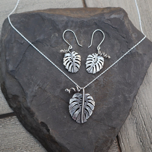Monstera deliciosa necklace and earring set made from sterling silver from The Striped Cat Metalworks. The jewelry is shown on top of a dark grey slate.