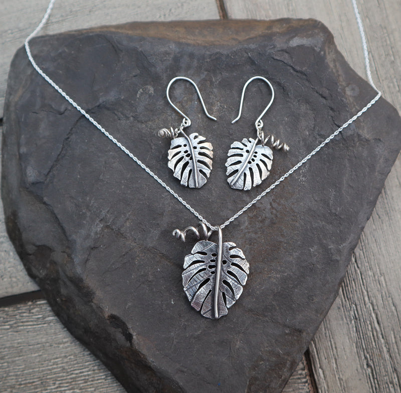 A monstera deliciosa earring and necklace set shown on a piece of dark grey slate stone.