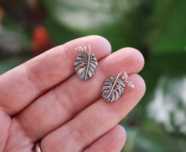 A hand is shown holding a pair of sterling silver monstera deliciosa earring studs. They earring are about 1/2 inch tall and have little twirled stems.