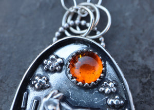 A close up of the natural amber gemstone at the top of a handmade moose pendant created by The Striped Cat Metalworks.