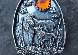 Sterling silver handmade mother moose and baby pendant made by The Striped Cat Metalworks. The pendant has an amber colored stone and shown on a slate piece of rock.