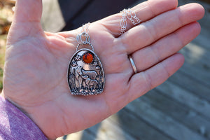 A handmade mother and child moose pendant shown in someone's hand to show the pendant's size. Made by The Striped Cat Metalworks.