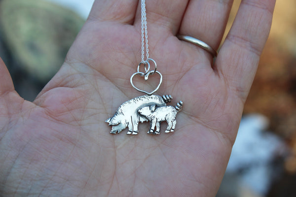 A hand holding the mother pig and piglet necklace for size reference.