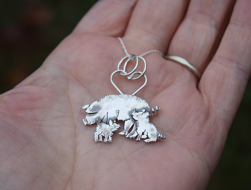 A mother pig with two piglets was a custom design pendant. It is shown in a hand for size.
