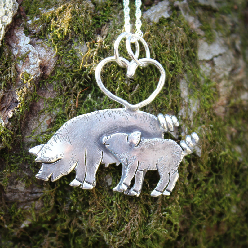 A mother pig and piglet necklace that is handmade from sterling silver. The little piglet is looking up at his mother. There is a heart at the top of the pendant that keeps the pendant on a necklace. It is shown on a moss piece of tree bark.