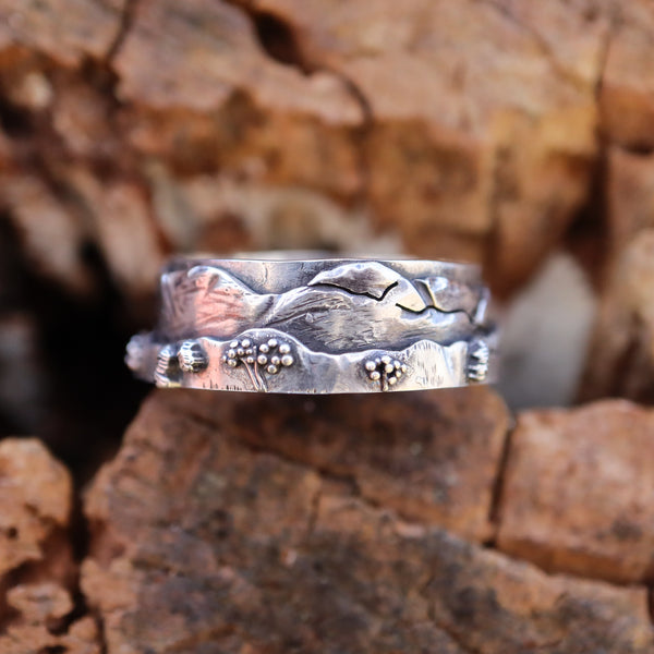 A sterling silver White Mountain range ring with tiny bushes, mountains, and a skyline The ring is shown on a piece of brown wood.