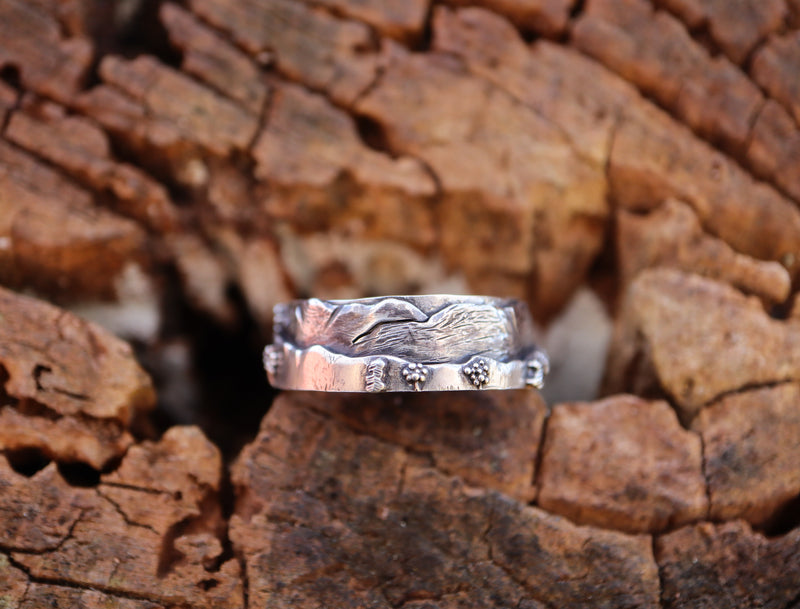 A sterling silver mountain ring shown on a piece of light brown wood.