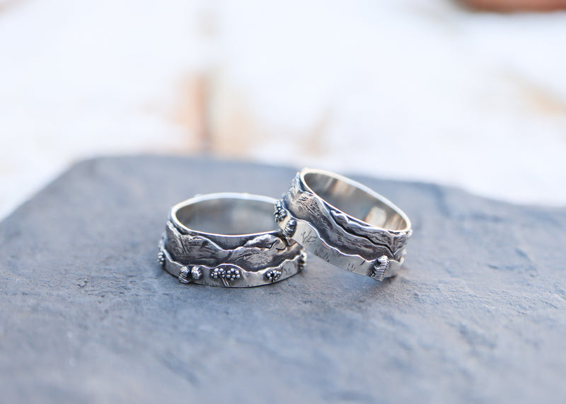 Two rings showing the White Mountains range on them. One of a kind rings made from sterling silver and shown on a piece of dark grey slate.