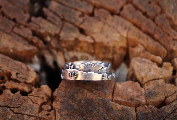 Another side of the White Mountains range ring in sterling silver. It is shown on a piece of brown wood.