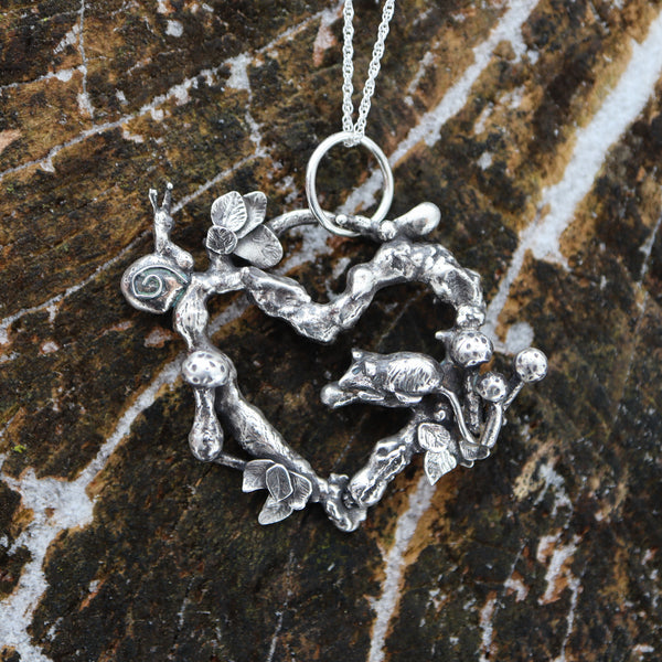 A snail and rat necklace that is made from recycled sterling silver. The little snail is sitting at the top of the tree branch heart and looking all around. The rat is sitting down below the snail and has some mushrooms behind him. There are mushrooms and leaves all over the piece as well.