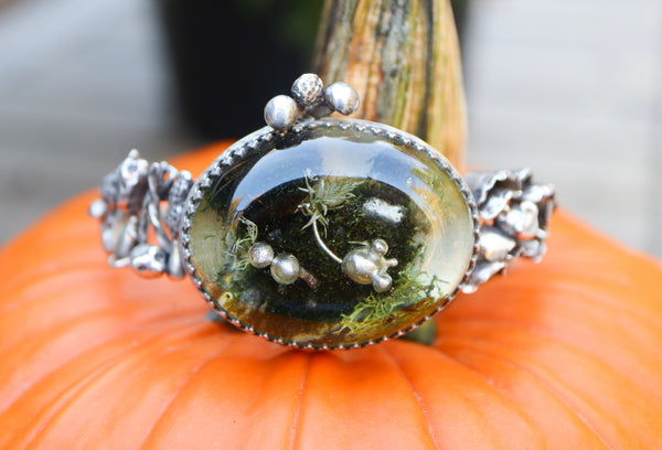 A sterling silver and resin cuff bracelet made with little tiny mice and mushrooms all over it. It is shown on top of an orange pumpkin.