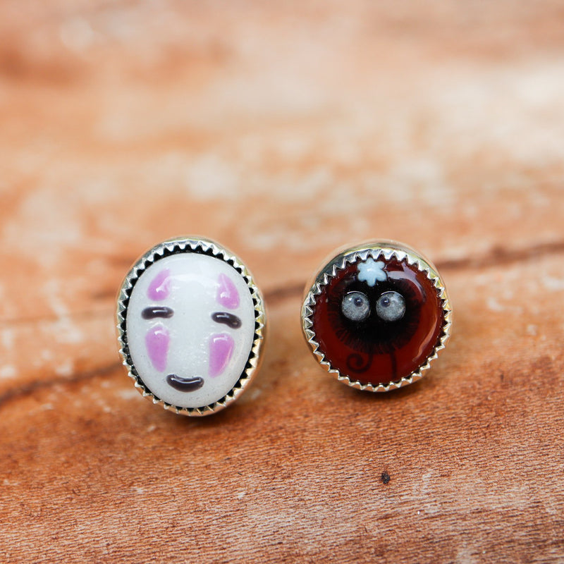 Handmade glass art cabochons made into sterling silver earrings by Abigail Castagnaro and Tamara Castagnaro. These earrings are about 1/2 inch tall and feature No-Face and a black soot sprite from Miyazaki films.