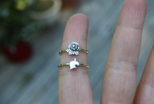 A pansy ring and a tiny Nook leaf ring being worn on a finger to show size.