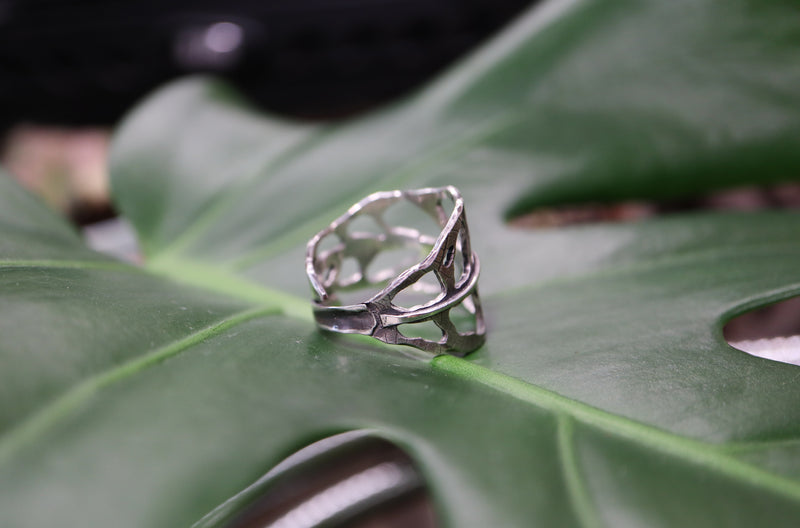 The side view of a handmade sterling silver monstera obliqua leaf.