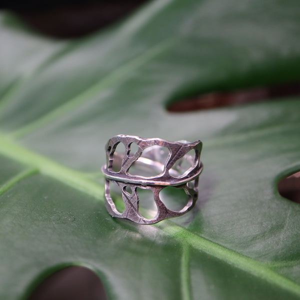 Sterling silver monstera obliqua ring shown on a green plant leaf.