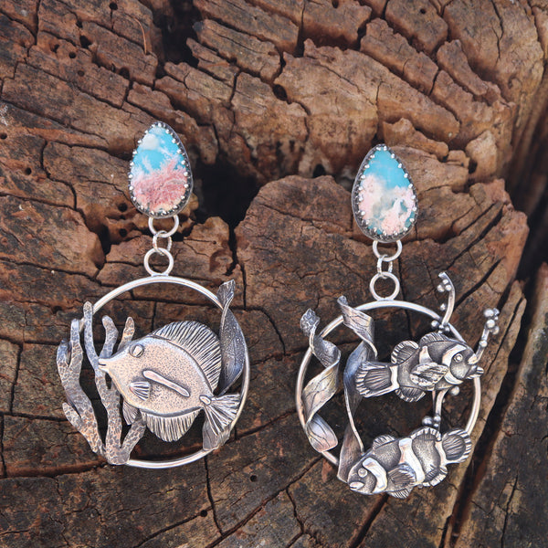 A pair of larger sterling silver handmade ocean earrings featuring a yellow tang on one and two clownfish on the other. There are beautiful ocean blue backed stones with coral like plume agates in front. The fish are in circle hoops and hang from the teardrop shaped stones. They are shown on a piece of light brown tree bark.