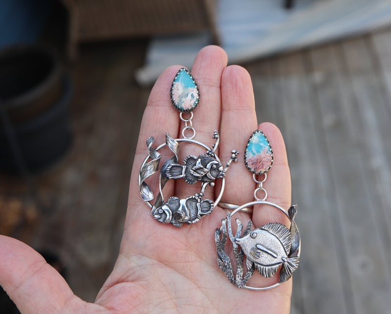 A hand is shown holding both of the earrings to show size. The earrings are each about 3 inches tall.