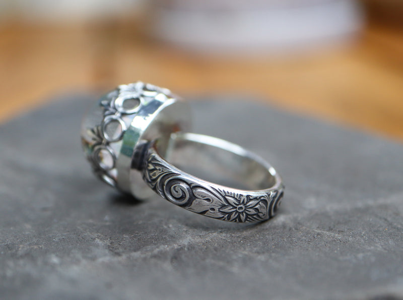 A close up of the sterling silver band for the white opal ring. It is shown on a dark grey piece of stone.