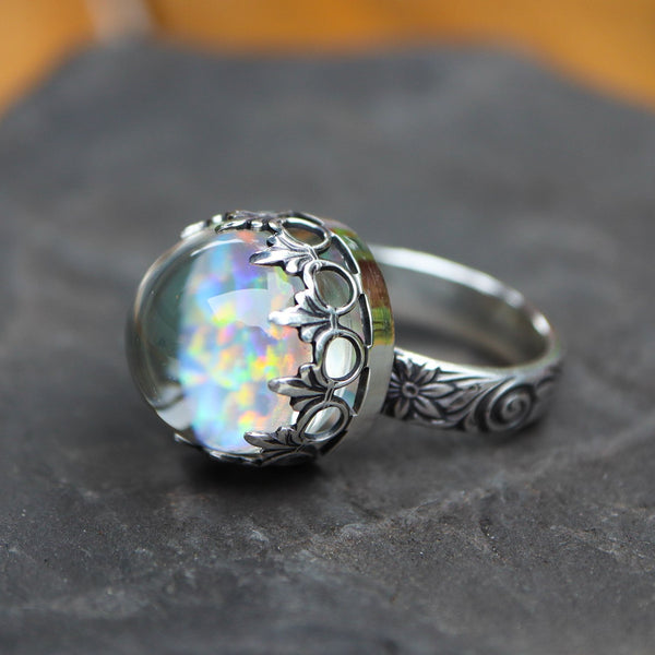 A glass white opal boro ring made with sterling silver in a size 8 shown on a dark grey piece of stone.