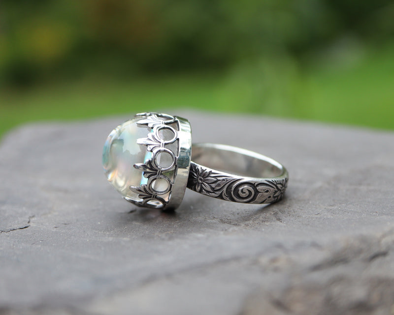 Another view of the side of a white glass opal ring made with sterling silver in a size 8.