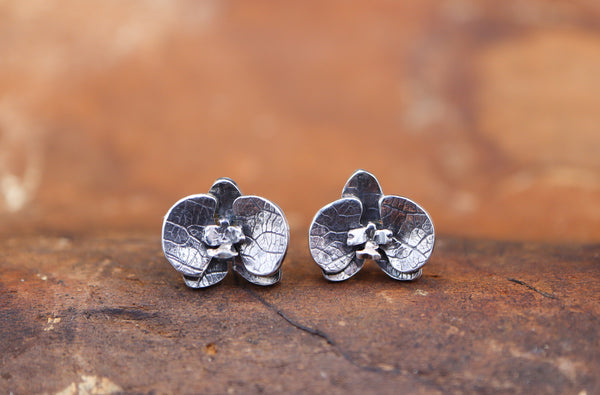 Handmade sterling silver orchid flower stud earrings shown in a piece of dark brown wood.