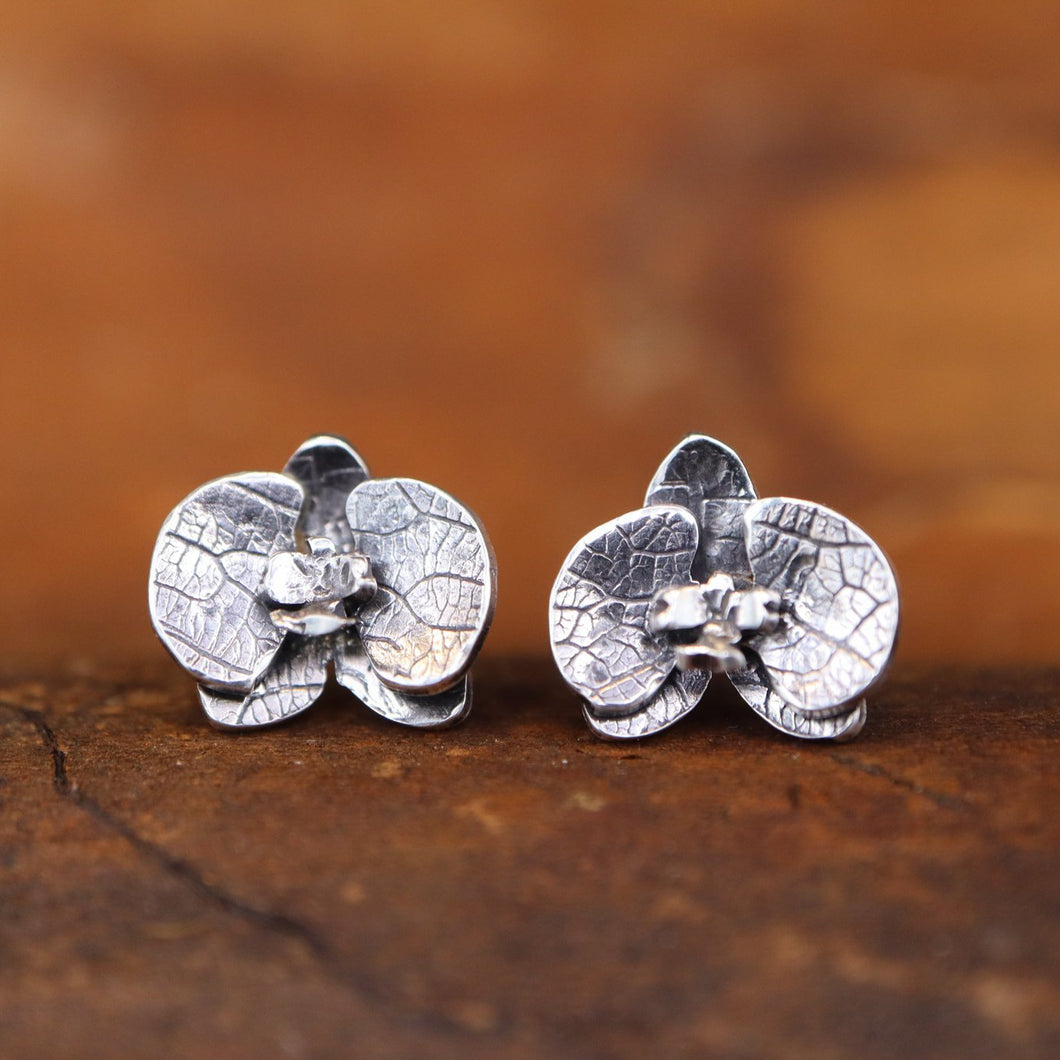 Tiny orchid earring studs made from sterling silver. They are shown in a dark brown piece of wood.