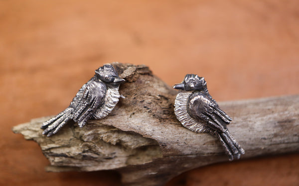 Tiny handmade sterling silver phoebe bird earrings are shown on a light brown stick.