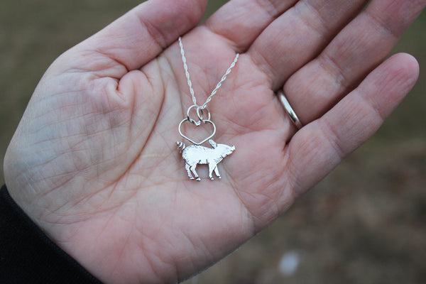 A hand is shown holding a tiny sterling silver piglet necklace.