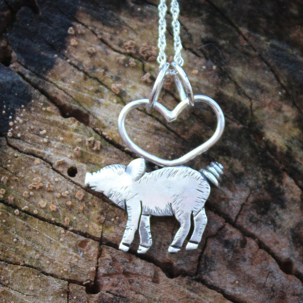 A tiny handmade sterling silver piglet necklace. It is shown on a dark brown piece of tree bark.