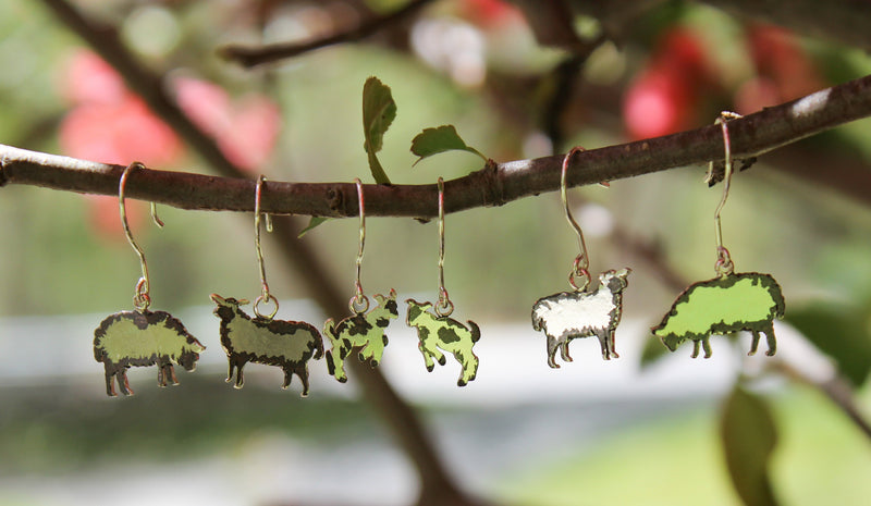 3 pairs of earrings shown on a tree branch outside. 2 pairs of earrings are of sheep and 1 pair is of silly goat babies.