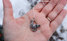 Load image into Gallery viewer, A hand holding a small sterling silver duck necklace for size reference.