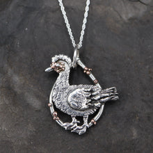 Load image into Gallery viewer, A handmade sterling silver and copper muscovy duck pendant. It is about 1 inch tall and shown on a dark grey slate stone.