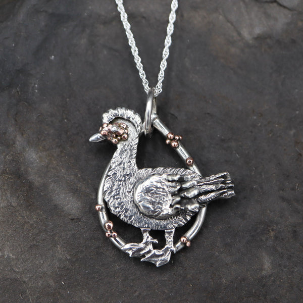 A handmade sterling silver and copper muscovy duck pendant. It is about 1 inch tall and shown on a dark grey slate stone.