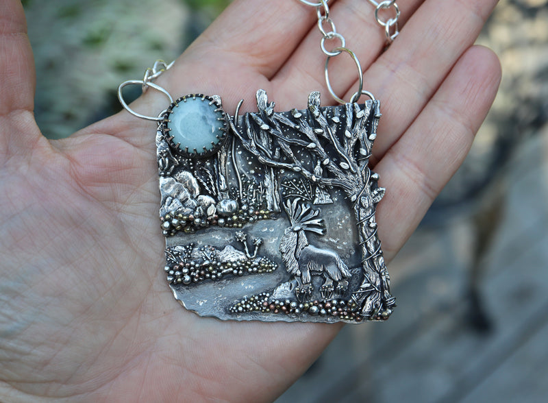 A close up view of a Princess Mononoke pendant shown in someone's hand for size. It features a glass glow in the dark moon and the Forest God from the Studio Ghibli film.