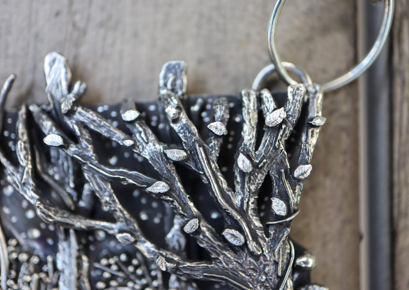 A close up of one of the trees in the Princess Mononoke pendant showing lots of tiny leaves and tree branches.