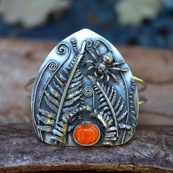 A one of a kind sterling silver Halloween bracelet featuring a hand carved jumping spider and she is surrounded by 3 dimensional ferns. At the bottom of the bracelet is a hand made glass pumpkin in a bright orange.