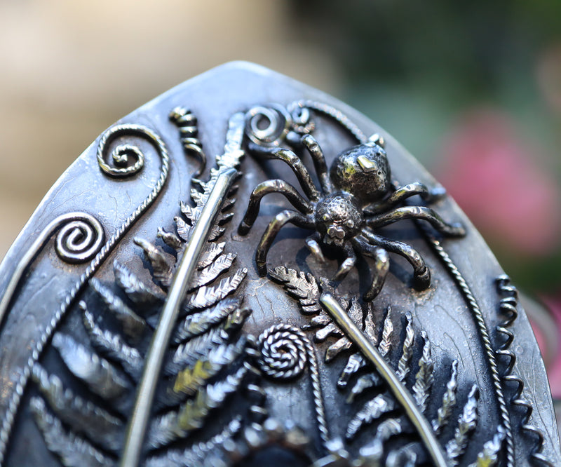 A close up photo of the 3 dimensional hand carved jumping spider. She is surrounded by frilly silver ferns.