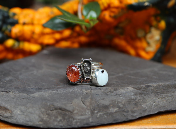A set of three handmade rings. A deep orange sparkly Oregon sunstone, a little silver coffin with a tiny ghost inside, and a glass glow in the dark white pumpkin with a fancy copper and silver band.
