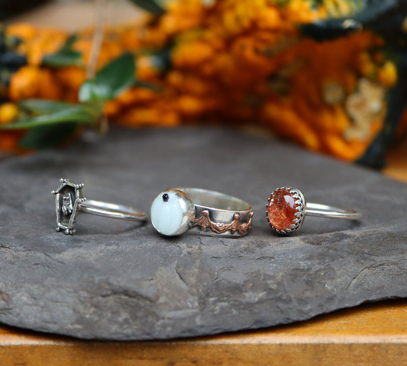 The side views of the three rings showing the bands. They are shown in a dark grey piece of stone with orange and green gourds behind them out of focus.