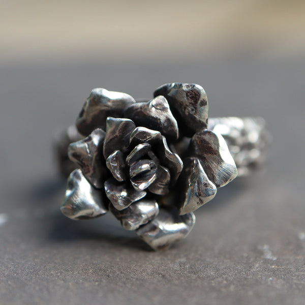 A handmade sterling silver rose flower ring. It is a close up of the hand fabricated flower.