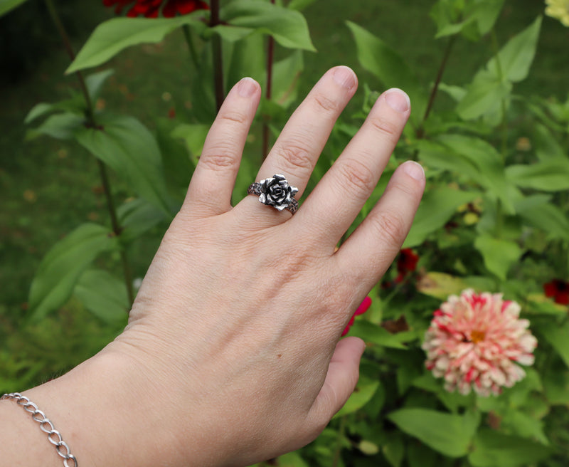 A hand is wearing the sterling silver rose ring to show what it looks like being worn. There are green leaves and striped zinnias in the background.