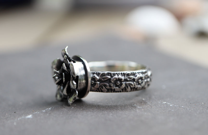 A side view of the sterling silver rose ring. The ring's band is a thicker silver flower pattern. It is shown on a piece of dark grey and white stone.