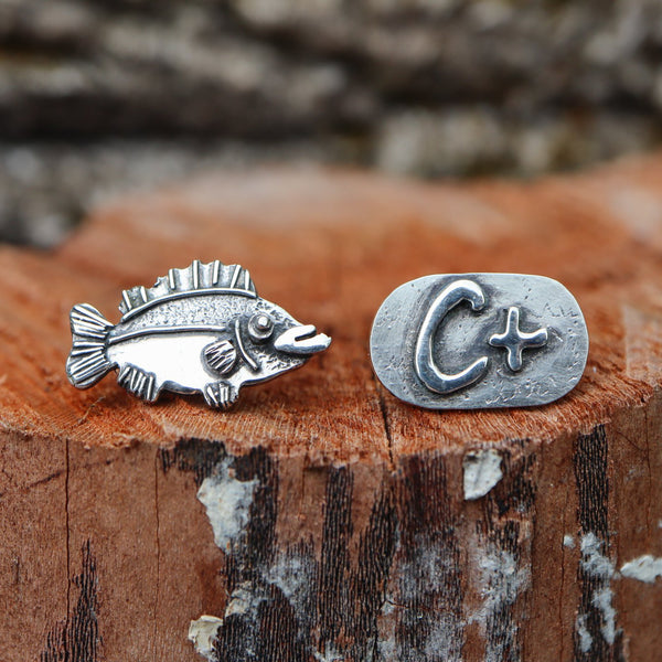 Animal Crossing stud earrings that are mismatched. One is a sea bass and the other earring says C+ on it. They are both about 1/2 inch wide and shown on a piece of light brown wood.
