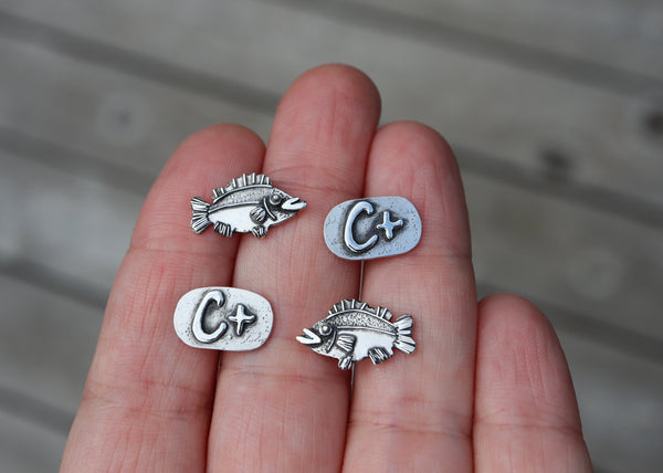 Animal Crossing stud earrings made from sterling silver and show in a hand for size reference. They are about 1/2 inch wide.