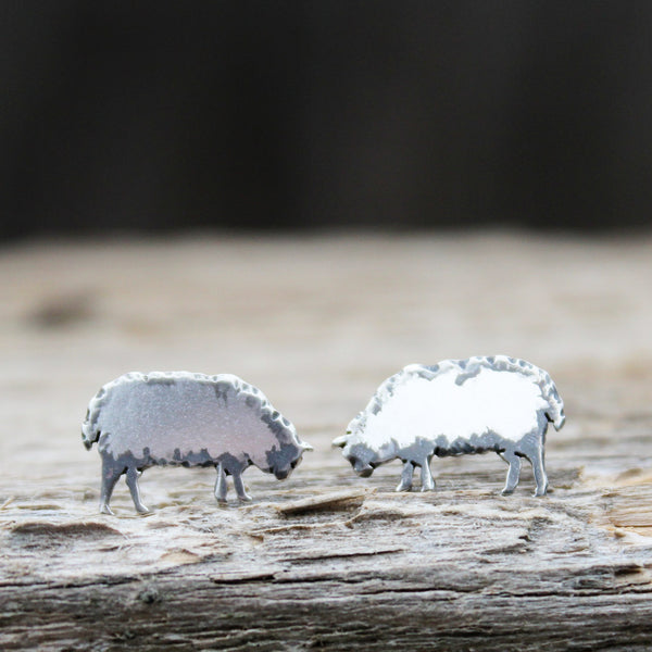 Handmade sterling silver sheep earrings that look like they are bending their head down to eat grass. They are shown on a piece of wood.