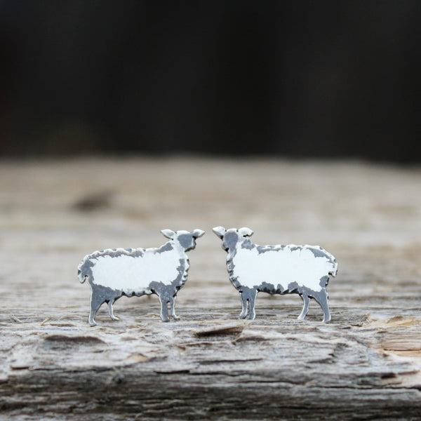 Sterling silver handmade sheep earrings made to look fluffy. They are shown on a piece of light brown wood.