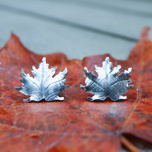 Sterling silver maple leaf stud earrings are shown on top of a bright orange fall maple leaf.