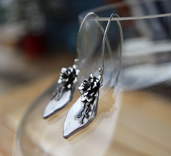A side view of the mother succulent leaf earrings. There is a baby plant at the top of the mother leaf like they grow when they are propagating.
