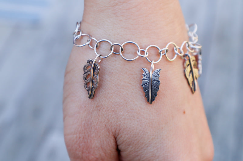 A handmade bracelet created by The Striped Cat Metalworks featuring 5 different popular houseplant leaf charms. It is shown being worn on a wrist with three of the leaf charms showing.