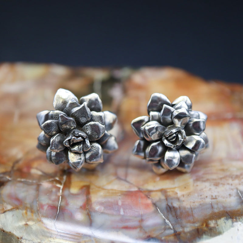 sterling silver handmade succulent earrings are shown on top of a light brown chunk of petrified wood.